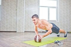 Fitness man does push-ups on the ball. At hall with window, workout lifestyle concept stock photos