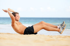 Fitness man doing crunches sit-ups on beach. Exercise outside. Fit male athlete exercising sit ups training on beautiful beach. Handsome sport model in cross Stock Image