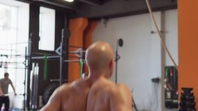 Fitness man doing jumping rope training in gym. Fitness man with naked torso doing jumping rope training in gym stock footage