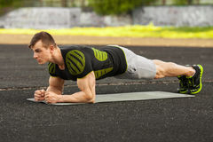 Fitness man doing planking exercise in the stadium, muscular male workout, outdoors Royalty Free Stock Images