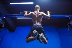 Fitness man doing pull-ups in a gym for a back workout back view.  stock photo