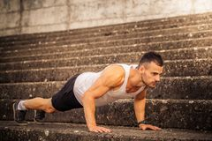 Fitness man doing push up. Young, muscular athlete is doing a push up outdoor Royalty Free Stock Photos