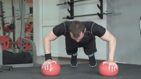Fitness man doing push-ups exercise on the ball in gym stock footage