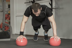 Fitness man doing push-ups exercise on the ball in gym Royalty Free Stock Images