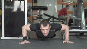Fitness man doing push-ups exercise intense training in gym. stock footage