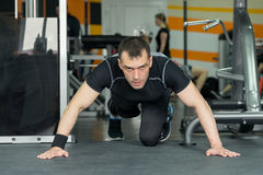 Fitness man doing push-ups exercise intense training in gym. Royalty Free Stock Photography