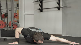 Fitness man doing push-ups in gym. Male doing exercise on the upper part chest of the body. Stock Photos