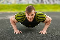 Fitness man doing push-ups in the stadium, cross training workout. Sporty male training outside Stock Photos