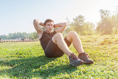 Fitness man doing sit ups and crunches exercising abdominal muscles. Stock Image