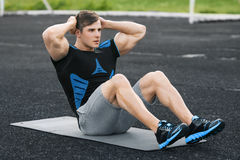Fitness man doing sit ups in the stadium, working out. Active male exercising abdominals.  Royalty Free Stock Photo