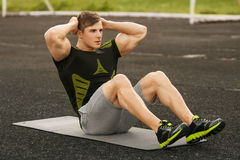 Fitness man doing sit ups in the stadium working out. Muscular male exercising abdominals, outdoor.  Royalty Free Stock Photography