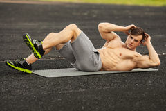 Fitness man doing sit ups in the stadium working out. Muscular male exercising abdominals, outdoor stock photos