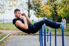 Fitness man doing stomach workouts on horizontal bar outdoors Stock Image