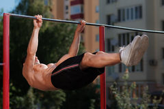 Fitness man doing stomach workouts on horizontal bar outdoors Royalty Free Stock Image