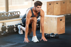 Fitness man doing stretching on the floor. In gym royalty free stock photography