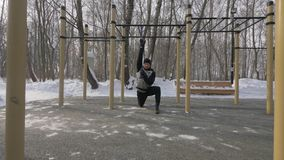 Fitness man doing workout exercises with expander on sports ground. For winter training. Male crossfit training for development strength and endurance stock video footage