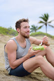 Fitness man eating healthy salad meal at workout Stock Photo