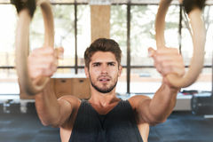 Fitness man is engaged on the rings. In gym stock photos