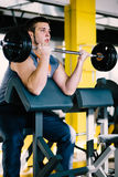 Fitness man exercising with barbell in gym. Fitness man dead lift. Sports and fitness - concept of healthy lifestyle. Stock Photos
