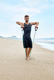 Fitness Man Exercising At Beach, Doing Expander Exercise Outdoor Stock Images