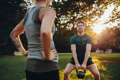 Fitness man exercising with personal trainer Royalty Free Stock Photo