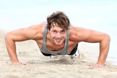 Fitness man exercising push ups. Smiling happy. Male fitness model cross-training on beach. Caucasian man in his twenties Royalty Free Stock Images