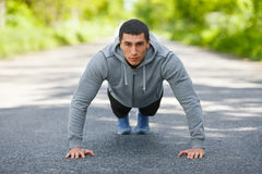 Fitness man exercising push ups, outdoor. Muscular male cross-training on city park Royalty Free Stock Photo