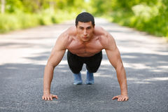 Fitness man exercising push ups, outdoor. Muscular male cross-training on city park Stock Photos