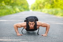 Fitness man exercising push ups, outdoor. Muscular male cross-training on city park Royalty Free Stock Images