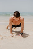 Fitness man exercising push ups smiling happy. Male fitness model cross-training on beach. Caucasian man in his twenties Royalty Free Stock Photos