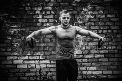 Fitness man exercising with stretching band in outdoor gym. stock photo