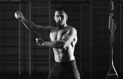Fitness man exercising with stretching elastic rubber band in the gym stock photography