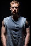 Fitness man in grey sleeveless shirt is sweating and looking at. Fitness men in grey sleeveless shirt is sweating and looking at you listening to music on Stock Photography