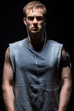 Fitness man in grey sleeveless shirt is sweating and looking. At you listening to music on earphones from the settled by armband device Stock Photo