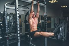 Fitness man hanging on horizontal bar performing legs raises, in the gym.  stock photography