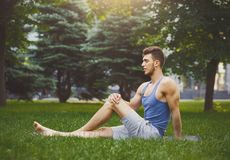 Fitness man have rest after training outdoors. Fitness man have rest outdoors. Young sporty guy sitting on grass after good training, copy space. Bodybuilding Royalty Free Stock Photos