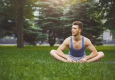 Fitness man have rest after training outdoors. Fitness man have rest outdoors. Young sporty guy sitting on grass after good training, copy space. Bodybuilding Stock Photography