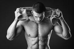 Fitness man. Holding a orange towel against dark background.Strong Athletic Man Fitness Model Torso showing abs. holding towel royalty free stock photography