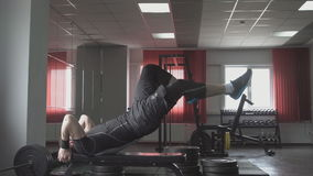 Fitness man is lying on the bench and raises his legs. Core cross training working out abs muscles. stock video