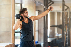 Fitness man makes selfie. In gym with weight stock photo