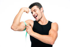 Fitness man measuring his biceps. Happy fitness man measuring his biceps isolated on a white background stock image