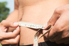 Fitness man measuring his body. Cropped and mid-section image of. Young man measuring his waist with tape measure against out door background. Health and Stock Photography