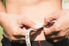 Fitness man measuring his body. Cropped and mid-section image of Royalty Free Stock Photos