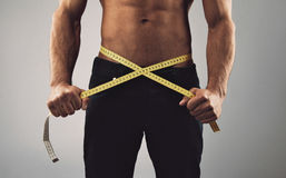 Fitness man measuring his waist. Fitness man measuring his body. Cropped and mid-section image of young man measuring his waist with tape measure against grey Royalty Free Stock Images