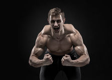 Fitness man model torso posing and showing perfect body. Shoulders, biceps, triceps and chest on black background Royalty Free Stock Images