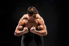 Fitness man model torso posing and showing perfect body. Shoulders, biceps, triceps and chest on black background Stock Photos