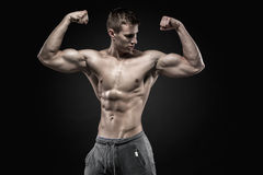 Fitness man model torso posing and showing perfect body. Six pack abs, shoulders, biceps, triceps and chest on black background Stock Image