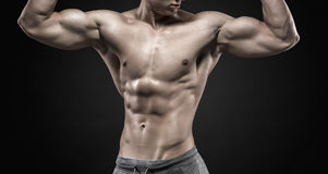 Fitness man model torso posing and showing perfect body. Six pack abs, shoulders, biceps, triceps and chest on black background. Close up Stock Images
