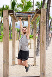 Fitness man on monkey bars fitness station gym Stock Photos