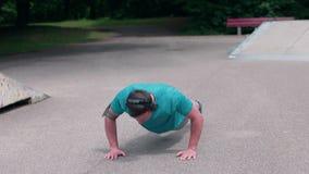 MUNICH, GERMANY - July 11, 2018  Fitness man plank workout training in park outdoors. Fitness man plank workout training in park outdoors. Young guy makes stock footage